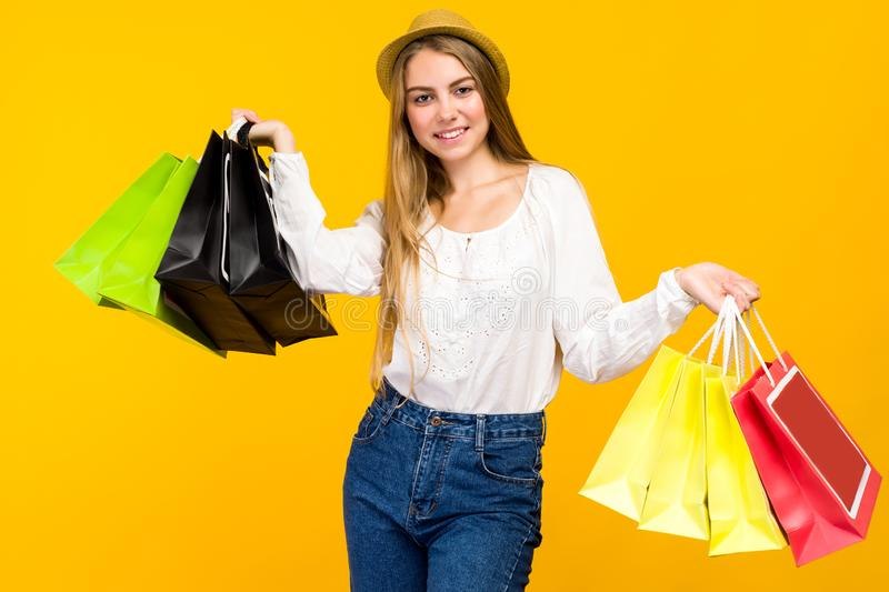 Caucasian teenage girl on yellow background. Stylish young woman with shopping bags in hands stock images