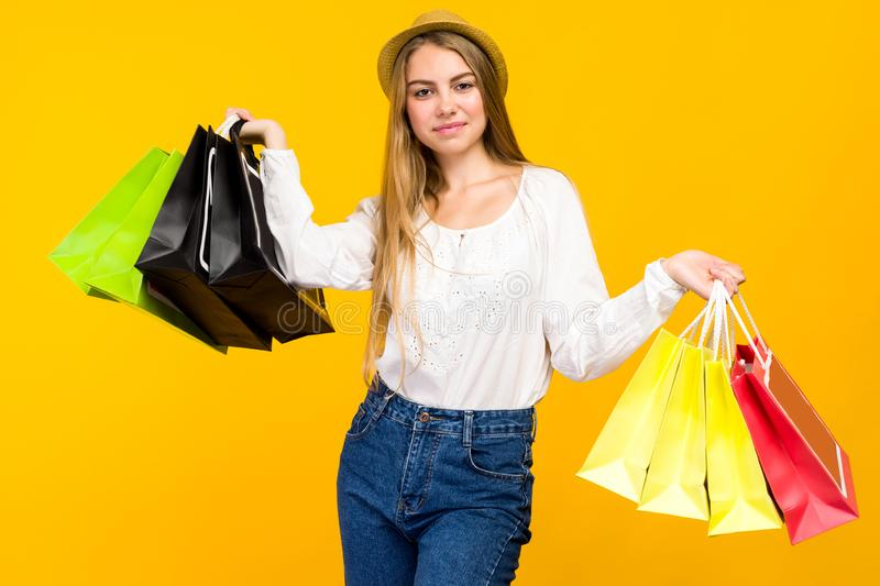 Caucasian teenage girl on yellow background. Stylish young woman with shopping bags in hands. Image, happy, holding, sale, friday, black, people, fashion royalty free stock photo