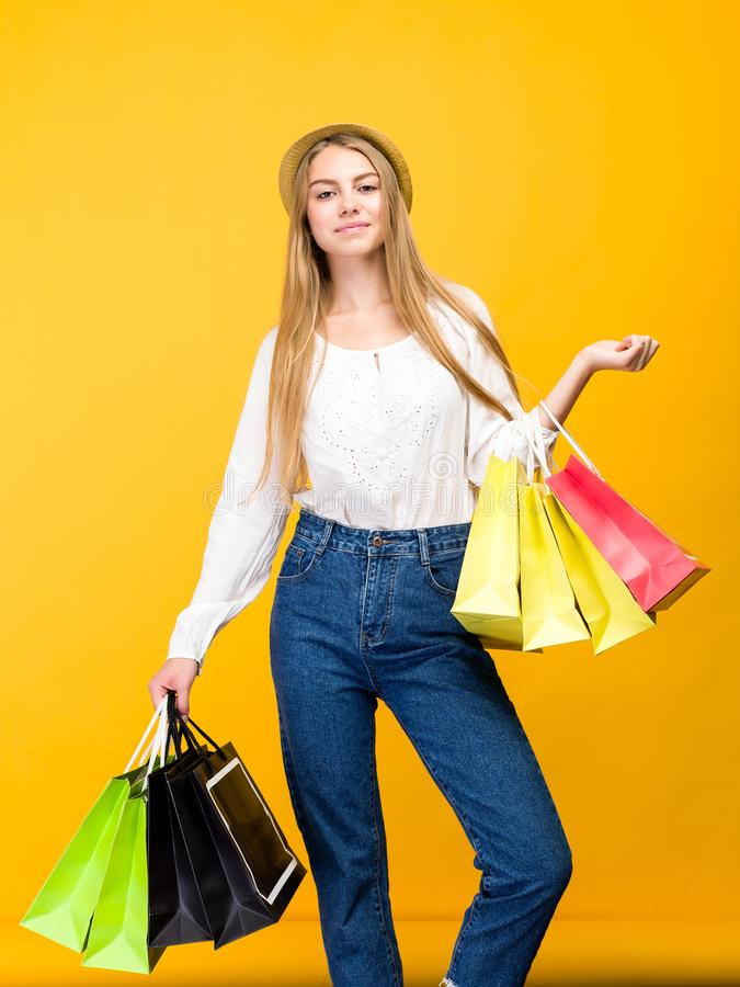 Caucasian teenage girl on yellow background. Stylish young woman with shopping bags in hands. Image, happy, holding, sale, friday, black, people, fashion royalty free stock photos