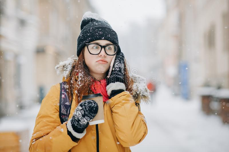 Outdoors winter portrait of beautiful teenage girl speaking on the phone royalty free stock photo