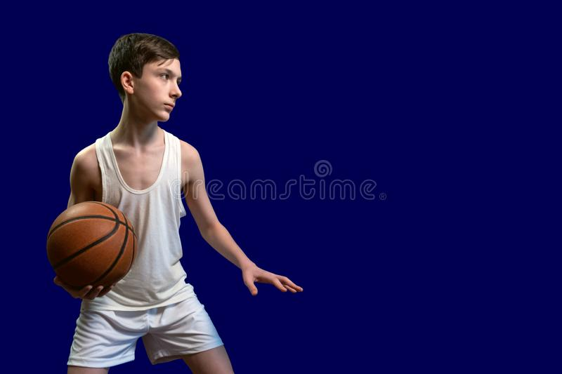 Caucasian teenager playing basketball. The guy in the white shirt is preparing to pass the ball to another player. Isolated on. Caucasian teenager playing stock images