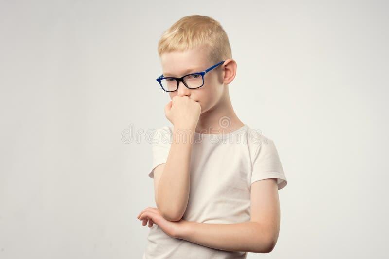 Caucasian tonåring med att tänka för blont hår som och för exponeringsglas isoleras på vit bakgrund royaltyfri fotografi
