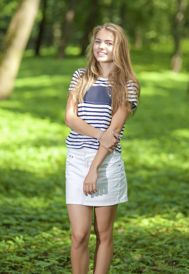 Caucasian tonåringflicka som poserar yttersidan i grön skog royaltyfri fotografi