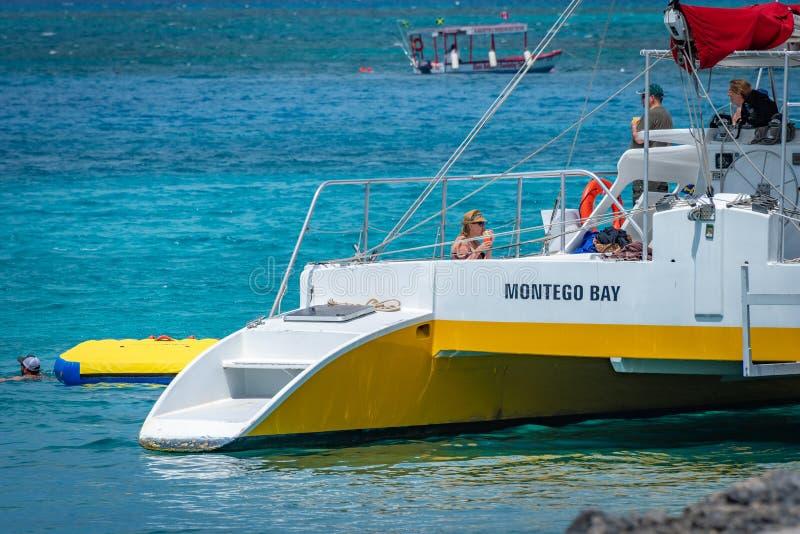 Caucasian turister som ombord tycker om drinkar på solig dag en katamaran i Montego Bay Jamaica arkivfoton