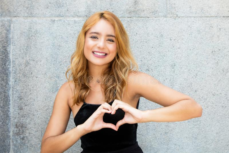 Caucasian ung förälskad visninghjärta för vuxen kvinna med händer royaltyfria bilder