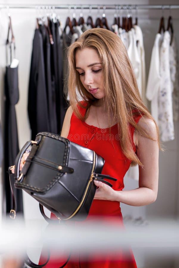 Caucasian ung kvinnlig shoppare som väljer läderryggsäcken från ny samling för kvinnor s arkivfoto