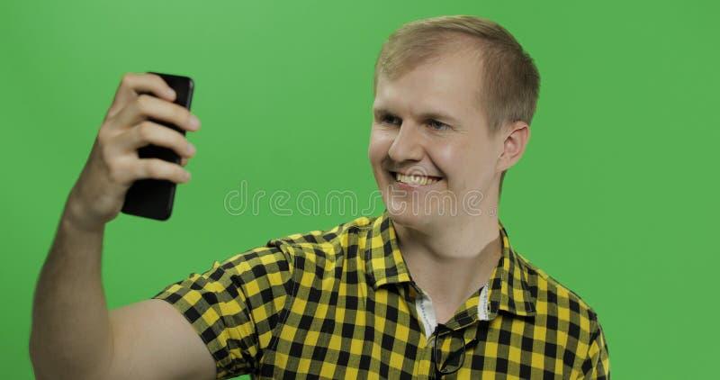 Caucasian ung man i den gula skjortan som tar trevliga selfies på smartphonen royaltyfria bilder