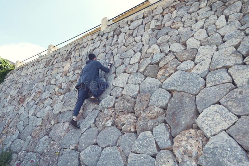Caucasian ung man som klättrar på en stenvägg i Banyalbufar Majorca royaltyfri foto