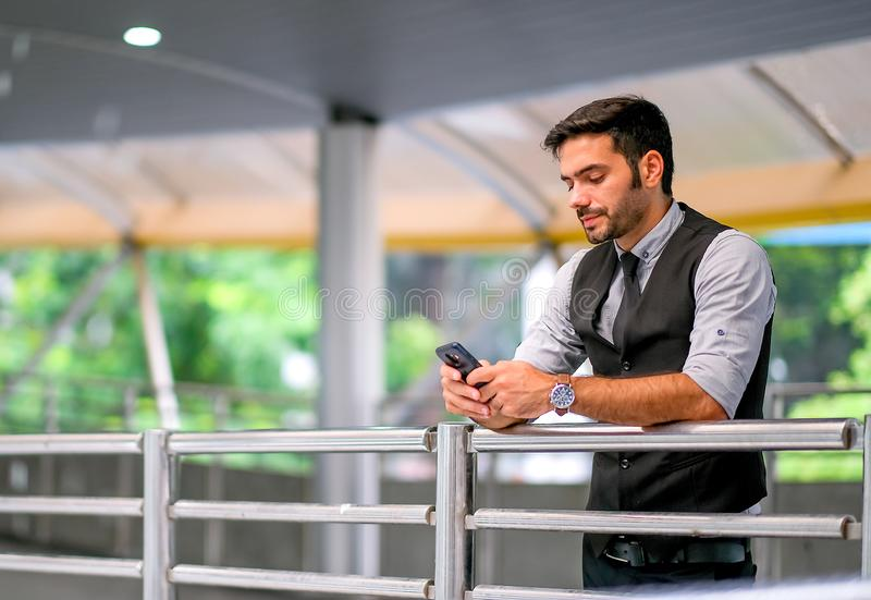 Caucasian white business man look at his mobile phone and stand at sky train walk way, also expressed sad emotion during day time royalty free stock photo