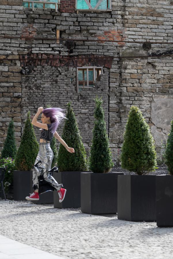 Caucasian white female model and brick stone. Beautiful girl with long purple hair resting in the city, modern fashion concept stock image