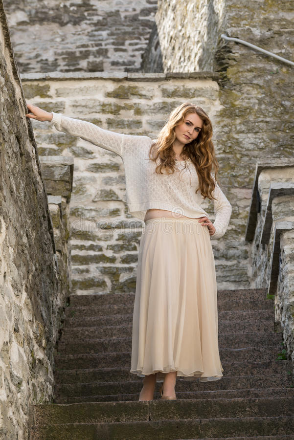 Caucasian white female model and brick stone. Beautiful girl, long red hair, beige skirt and cardigan. Woman standing on the stair stock image