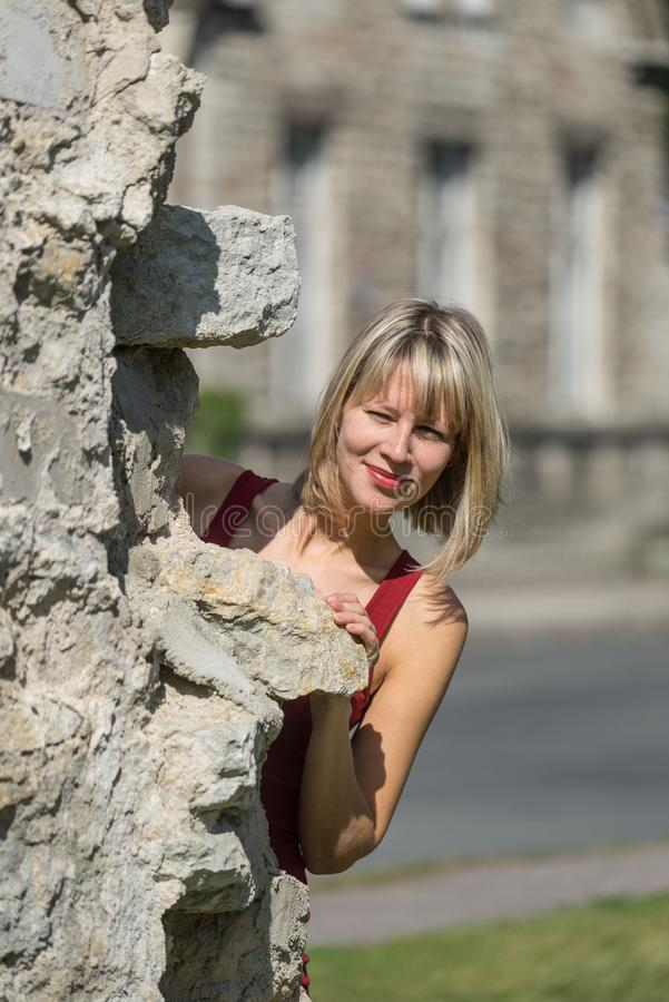 Caucasian white female model and brick stone. Woman in a red dress standing behind the wall in the city park stock photos