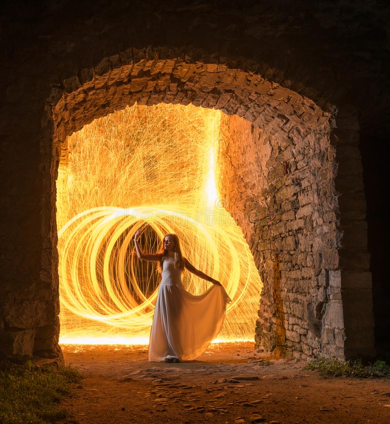 Caucasian white female model with long hair, in a white dress standing and throws gleaming sparks. Beautiful woman in old building surrounded by limestone wall stock images