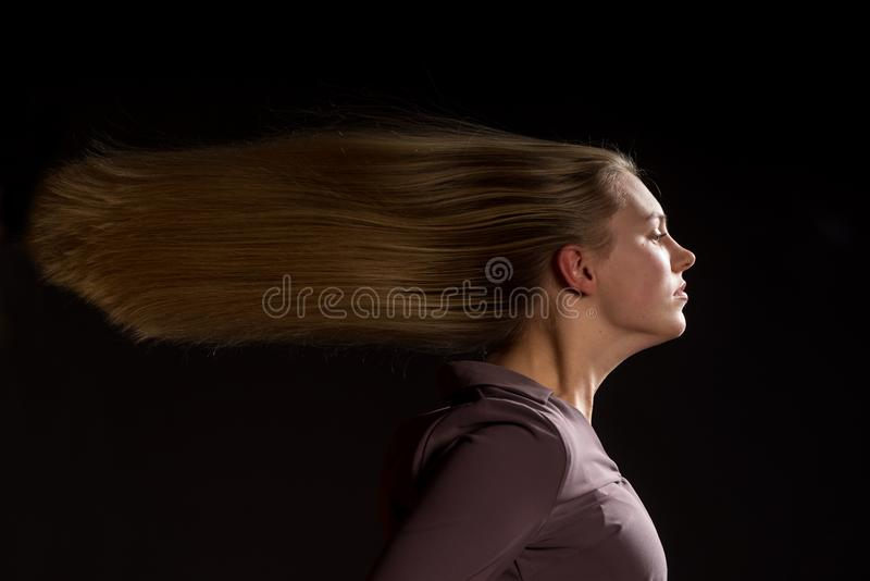 Caucasian white female model portrait. The wind blowing the long blonde hair off on beautiful girl. Woman posing studio shot stock photo