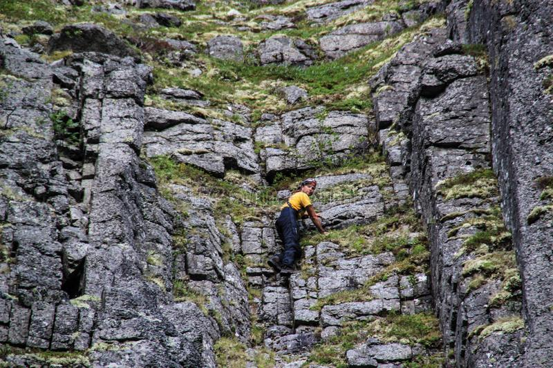 Caucasian white male rock climber in sportswear climbs stock images