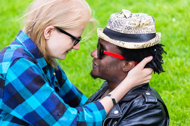 Caucasian woman and African man in loving embrace. Caucasian women and African men in loving embrace, looking in each others eyes as a couple royalty free stock image