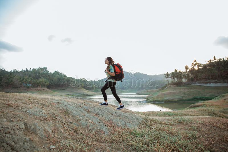Caucasian woman alone walking side lake. Carrying backpack stock image
