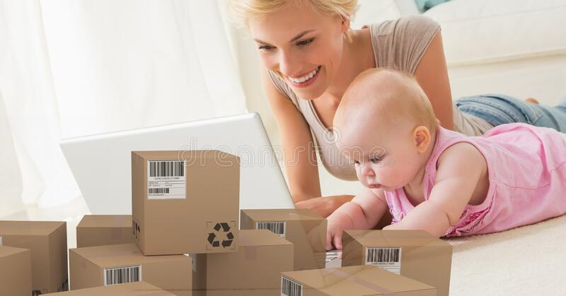Caucasian woman and baby girl using laptop computer and shopping online with pile of boxes. Caucasian woman and baby girl using laptop computer at home shopping stock images