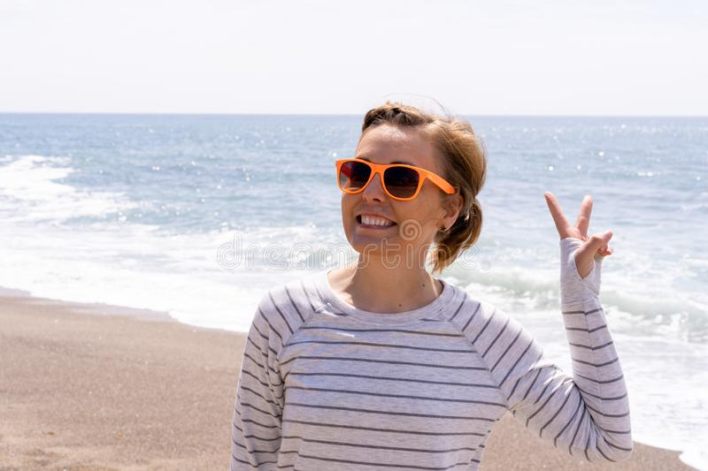 Caucasian woman on the beach gives a peace sign, wearing casual clothing and sunglasses.  royalty free stock photos