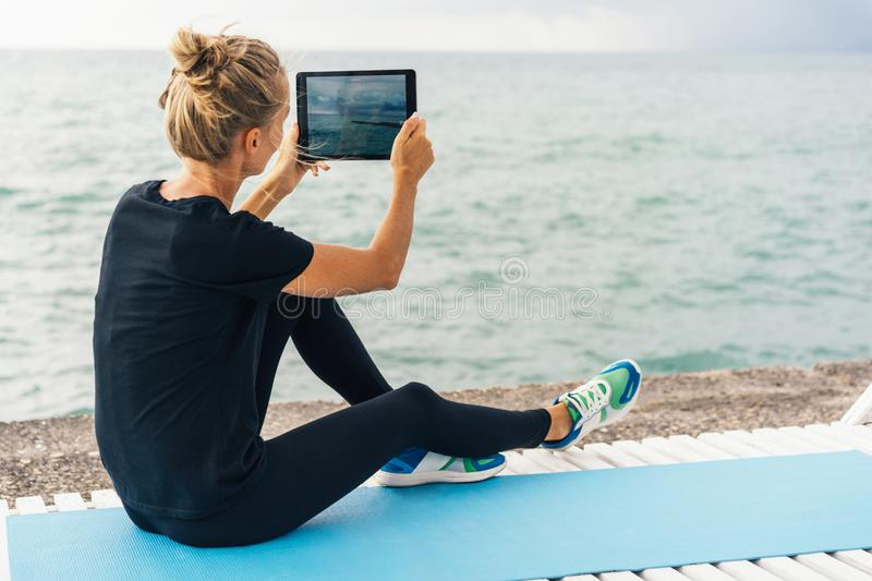 Caucasian woman blonde athlete during a break in training removes the story for the blog. royalty free stock photos
