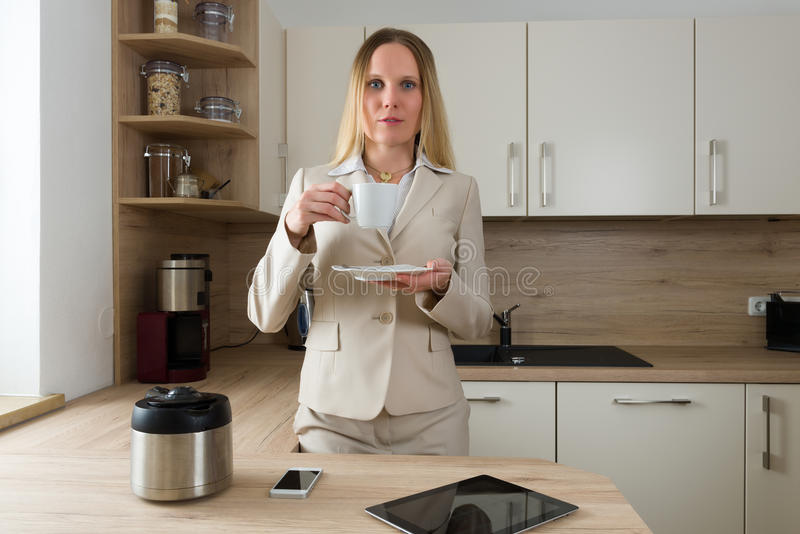 Caucasian woman in business suite drinking coffee in the kitchen royalty free stock image