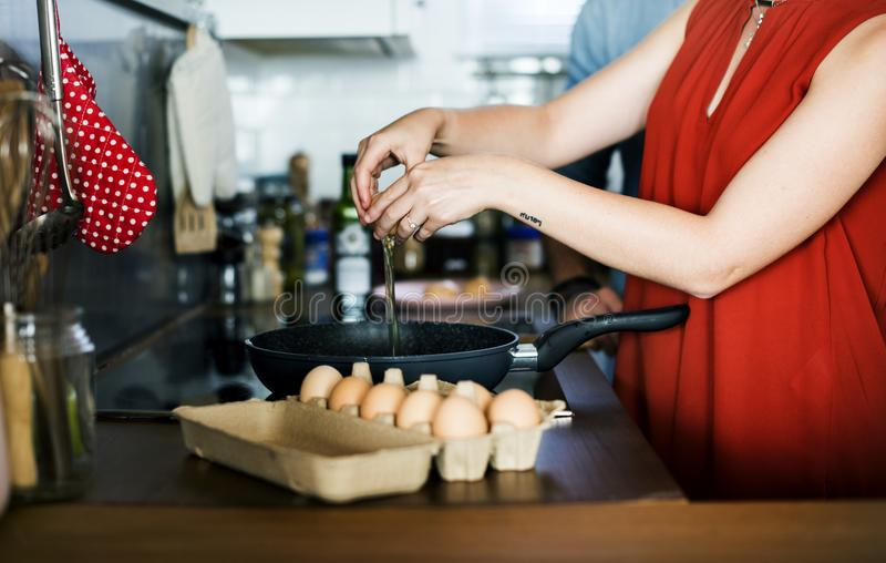 Caucasian woman cooking eggs in the kitchen stock images