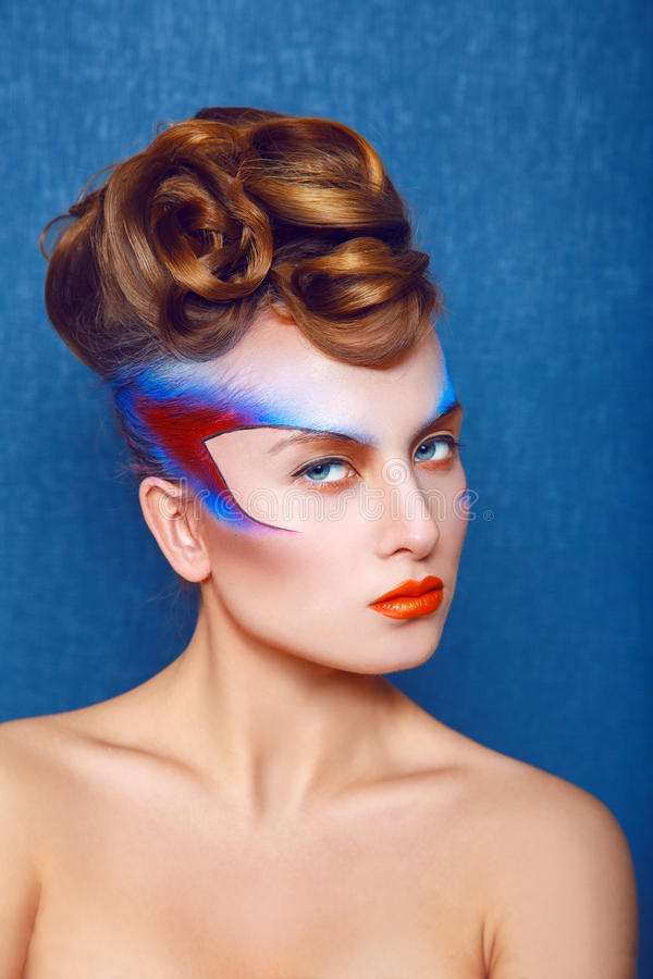 Caucasian woman with creative make up and hairstyle on blue back. Ground in studio royalty free stock images
