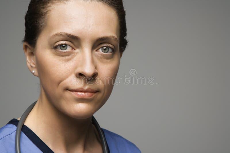 Caucasian woman doctor. Head shot portrait of Caucasian woman doctor against gray background stock image
