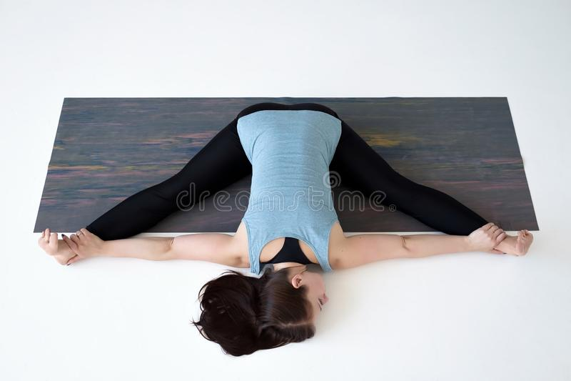 Caucasian woman doing yoga splits upavistha konasana on fitness mat. stock photos