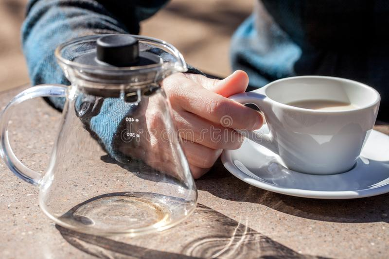 Caucasian woman hand holds ceramic cup with black tea and milk, empty glass teapot next to it stock images