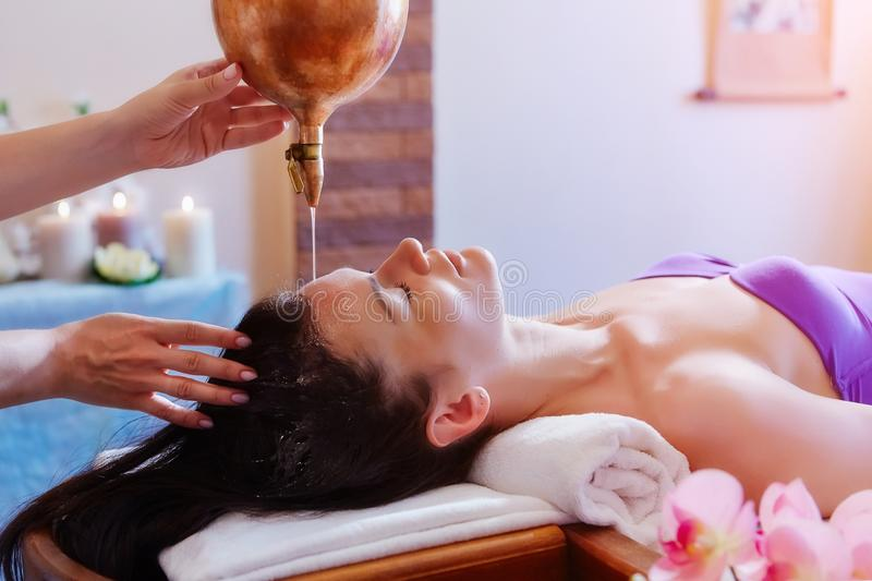 Caucasian woman having Ayurveda shirodhara treatment stock photography