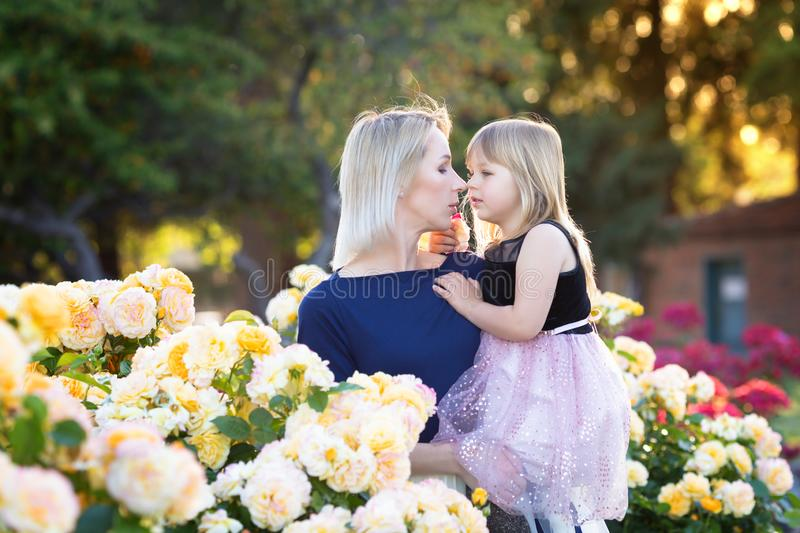 Caucasian woman with little girl in hands in rose garden, mommy and me concept, cuddling, looking to each other royalty free stock photography