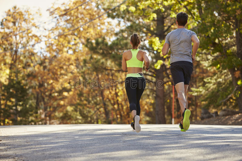 Caucasian woman and man jogging on a country road, back view. Caucasian women and men jogging on a country road, back view stock image
