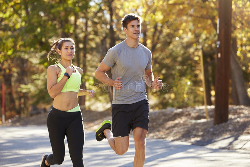 Caucasian woman and man jogging on a country road, close up. Caucasian women and men jogging on a country road, close up stock image