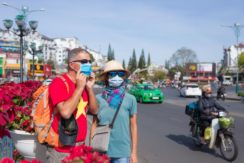 Caucasian woman and man wearing sanitary mask outdoors in Da Lat city centre Vietnam. Tourist couple with medical mask protection stock image