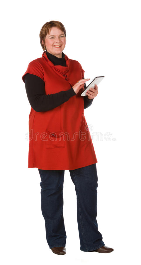 Caucasian woman in orange and blue. Caucasian woman in burnt orange top and blue denim with a tablet royalty free stock photo