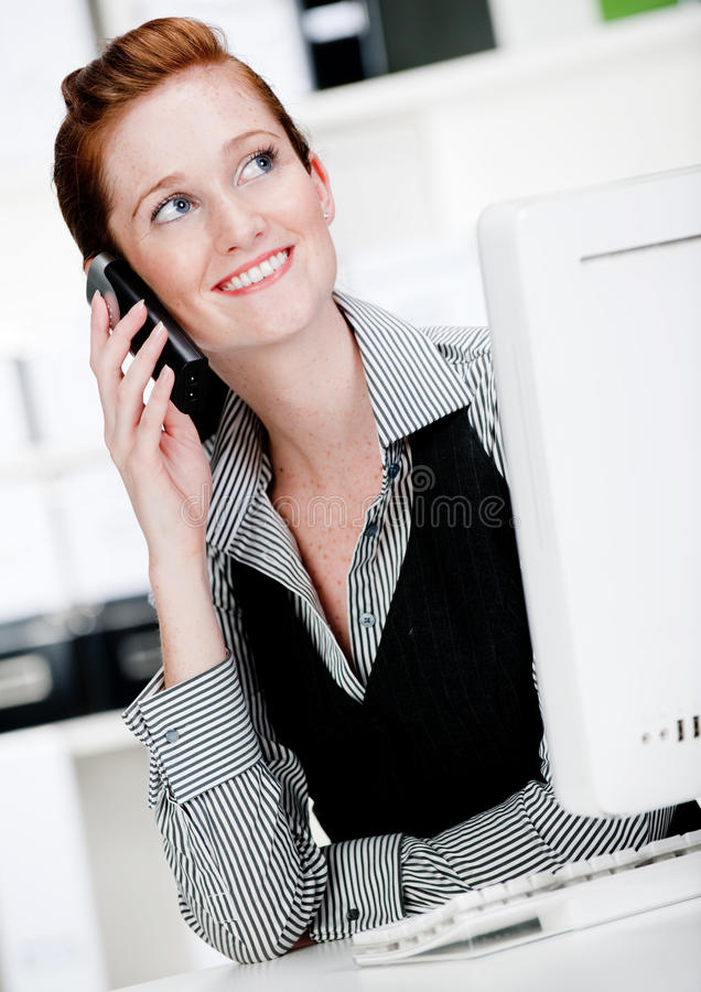 Caucasian Woman with Phone. An attractive caucasian woman using the phone in the office royalty free stock photos