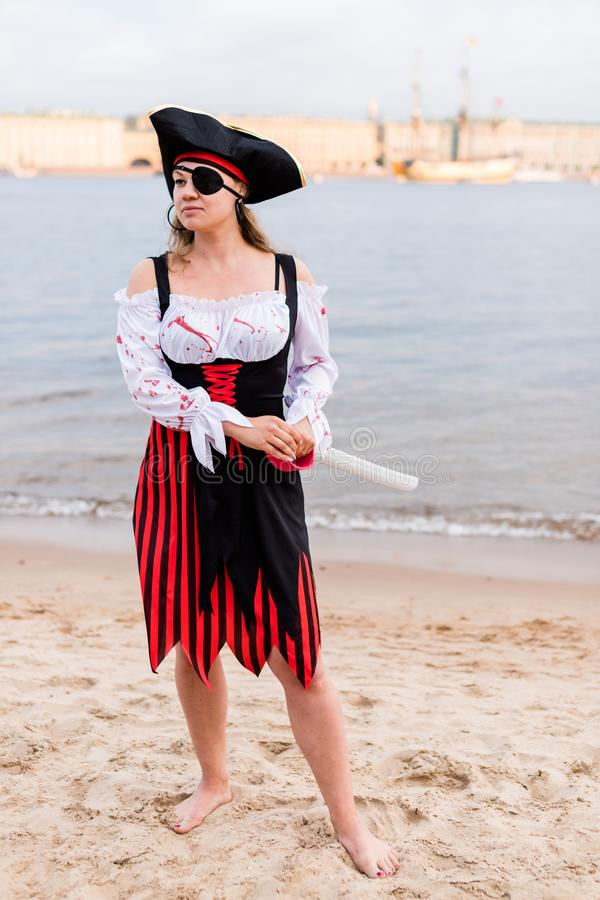 Caucasian woman in pirate costume with eye patch, cocked hat, sword on beach royalty free stock photos