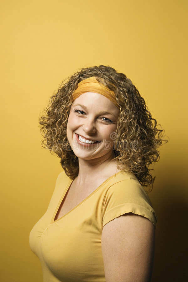 Caucasian woman portrait. Portrait of smiling young adult Caucasian woman on yellow background royalty free stock photos