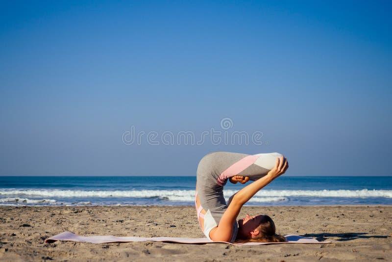 Caucasian woman practicing yoga at seashore morning summer beach stock photos