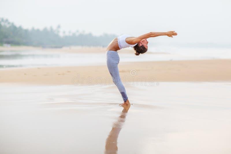 Caucasian woman practicing yoga at seashore of tropic ocean royalty free stock photo