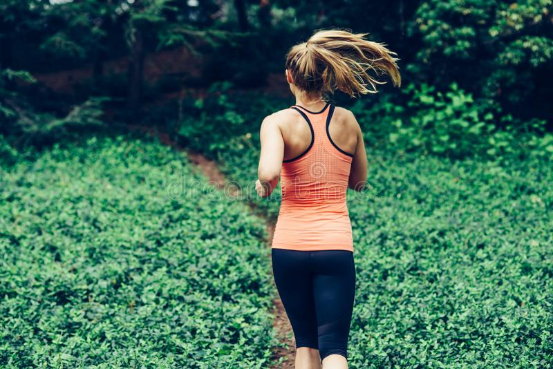 Caucasian woman running on forest trail wearing sport clothes royalty free stock photos