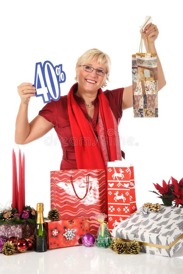 Caucasian woman, shopping bag discount. Cheerful middle aged caucasian woman behind the Christmas shopping, showing forty percent discount for the shopping from stock photos