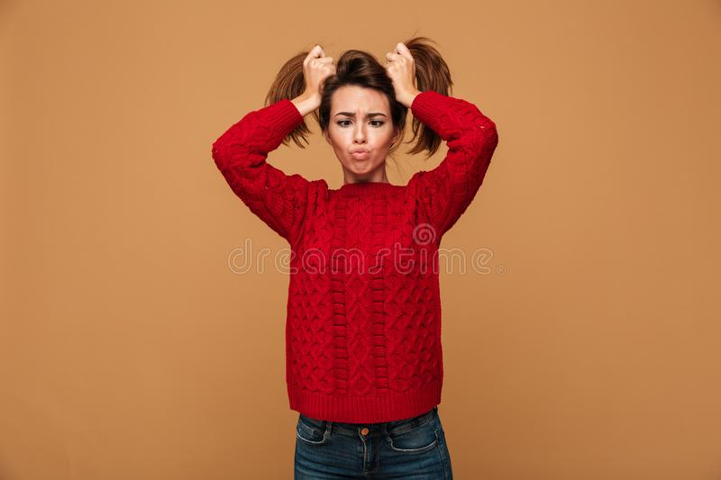 Caucasian woman showing funny emotions. Image of pretty caucasian woman dressed in sweater standing showing funny emotions stock image