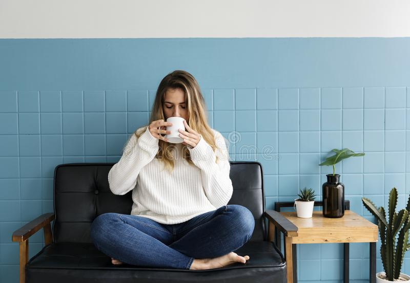 Caucasian woman sitting and drinking coffee stock photo
