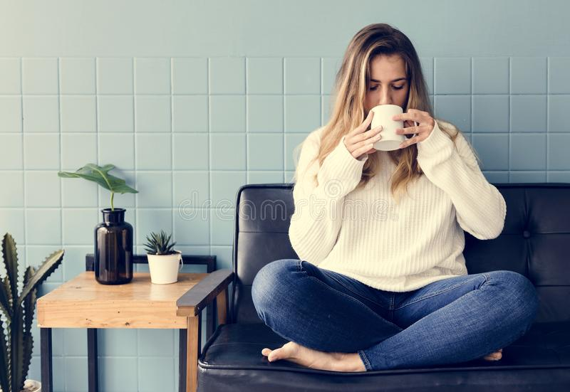 A Caucasian Woman Sitting and Drinking Coffee royalty free stock image