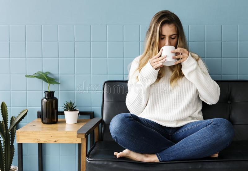 Caucasian woman is sitting and drinking coffee royalty free stock photos
