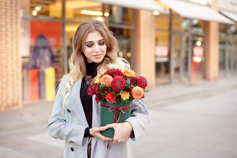 Caucasian woman standing on the street near storefront shop windows holding flower-box with happy smile. royalty free stock photos