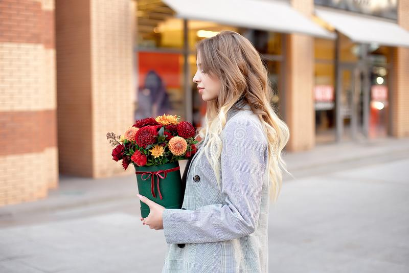 Caucasian woman standing on the street near storefront shop windows holding flower-box with happy smile. Caucasian woman standing on the street near storefront stock photo