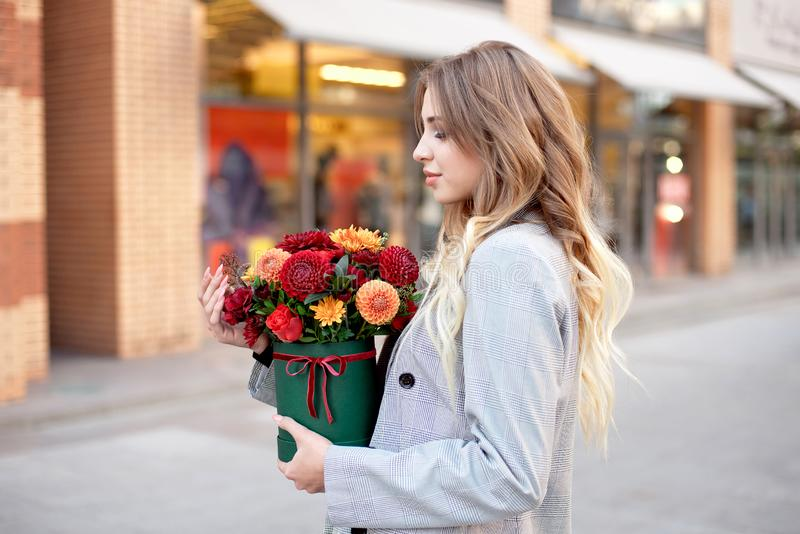 Caucasian woman standing on the street near storefront shop windows holding flower-box with happy smile. Caucasian woman standing on the street near storefront stock photography